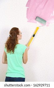 Young woman paints wall in new flat