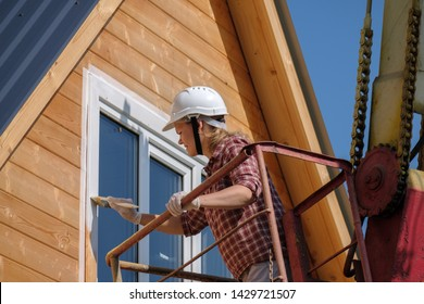 a young woman paints the window frames of a wooden house on the top floor with a aerial platform