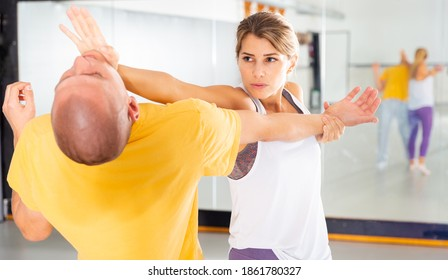Young woman paired up with male partner in self defense training, practicing basic palm strike