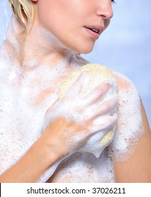 Young woman pampering her body with sponge and soap suds