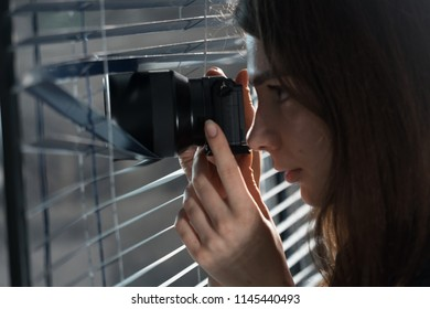 Young woman Paparazzi take a photo suspiciously from around a blinds  while using a camera. GDPR Concept