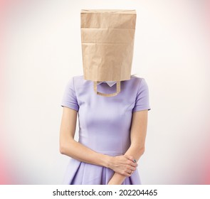 Young woman with paper bag over her head