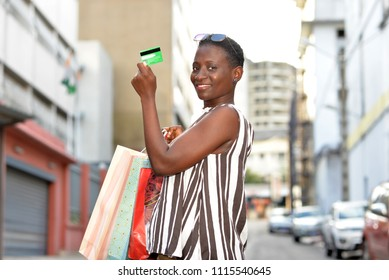 young woman with paper bags after shopping standing outside and smiles. showing a green credit card.
