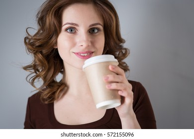 Young woman with a paper cup of coffee,