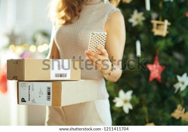young woman with parcels and smartphone using application near Christmas tree