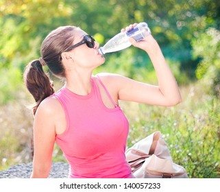 Young woman in park with bottle of water