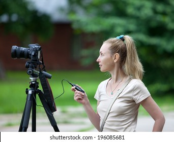 The young woman in park with the camera on a tripod.