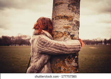 Young woman is in the park on a winter's day and is hugging a tree