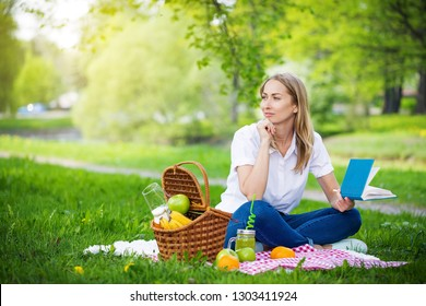 Young woman in park outside at sunny day, enjoying summertime and dreaming