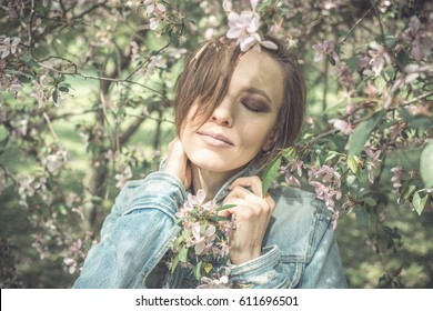 Young woman in a park with pink trees flower. toned image