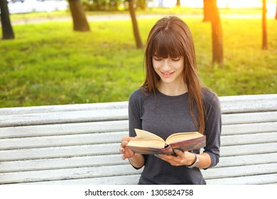 a young woman in the Park reading a book on a Sunny summer day