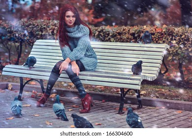 Young woman in park sitting on bench.