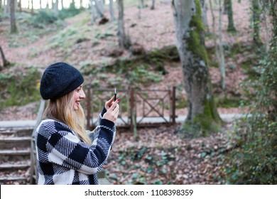 Young woman in park, taking a picture on mobile phone, smiling (selective focus)