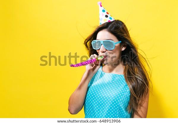 Giovane donna con cappello partito con rumoroso su uno sfondo giallo