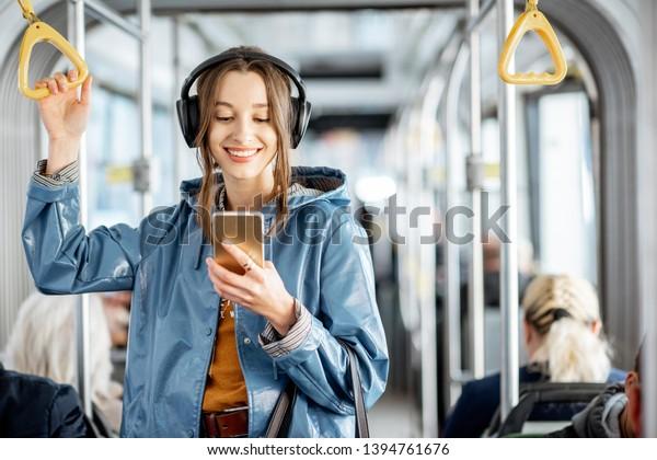Joven pasajera parada con auriculares y smartphone mientras se mueve en el moderno tranvía, disfrutando de un viaje en el transporte público