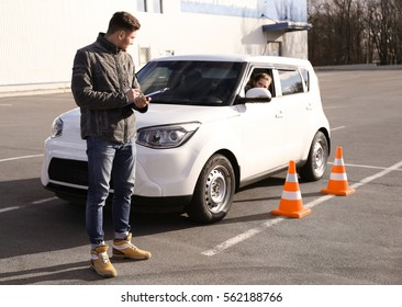 Young woman passing driving license exam outdoors