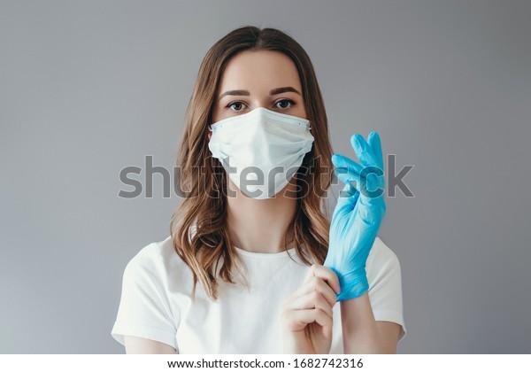 Jeune femme patiente sur un masque médical met sur son bras des gants de protection chirurgicale stérile, isolée sur fond gris, protection contre le coronovirus