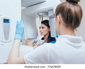 Young woman patient standing in x-ray machine. Panoramic radiography