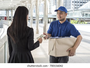 Young woman pay money and receiving parcels from courier