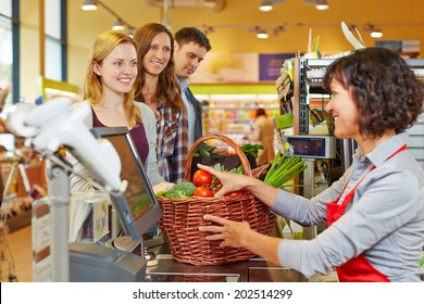 Young woman paying basket of groceries at supermarket checkout