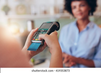 Young woman paying by credit card at juice bar. Focus on woman hands entering security pin in credit card reader.