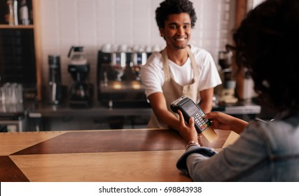 Young woman paying by credit card at cafe. Woman entering security pin in credit card reader with male barista standing behind checkout counter at coffee shop.
