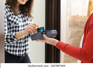 Young woman paying for food delivery with credit card