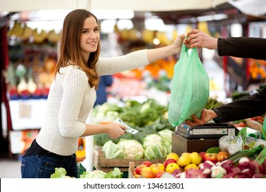 Young woman paying for vegetables at the market
