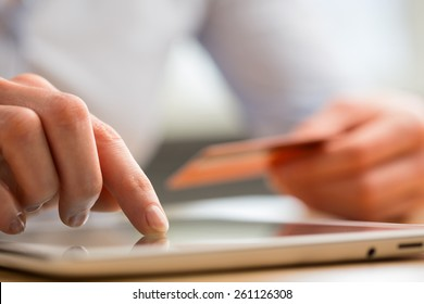 A young woman pays by credit card for an online purchase through a tablet computer.