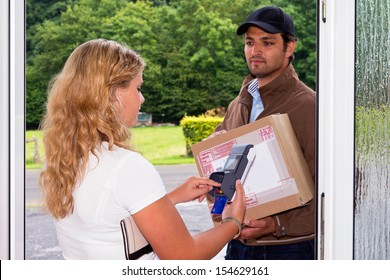 Young woman pays her cash on delivery parcel to a delivery postal worker using a portable, wireless ATM