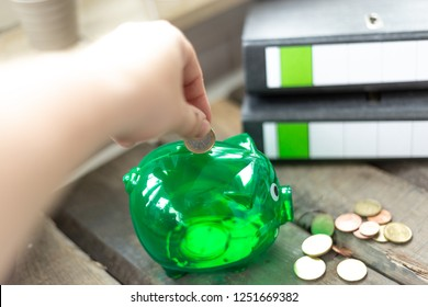 Young woman pays money to a green piggy Bank, energy savers