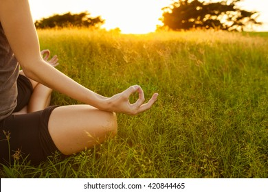 Young woman peacefully meditating in a open field.