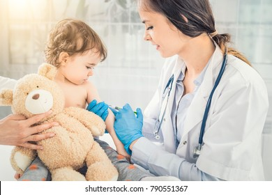Young woman pediatrician performs a vaccination of a little girl. The girl is holding a mascot.