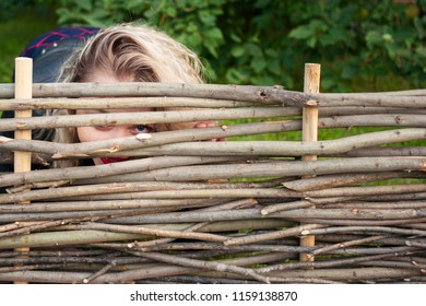 Young woman peeking over  fence