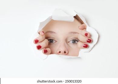 young woman peeking through hole in paper wall