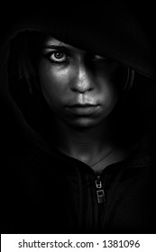 A young woman peering out from her hood, hiding in the shadows.