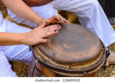 Young woman percussionist hands playing a drum called atabaque during brazilian folk music performance