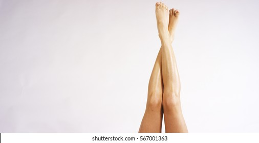 The young woman with perfect body with crossed smooth silky legs after depilaton on a white background. Concept of depilation, smooth skin, skincare, cosmetics, wellness center,healthy lifestyle