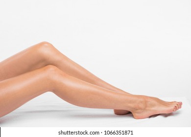 Young woman with perfect body is sitting with smooth silky legs after shaving on a white background.Concept of depilation, smooth skin, skincare, cosmetics, wellness center, and healthy lifestyle