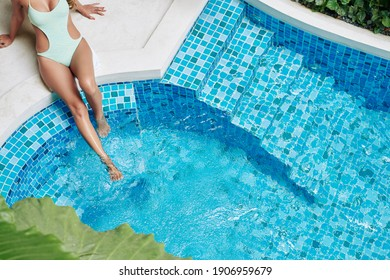 Young woman with perfect fit body splashing water in swimming pool when sitting on its edge, view from above