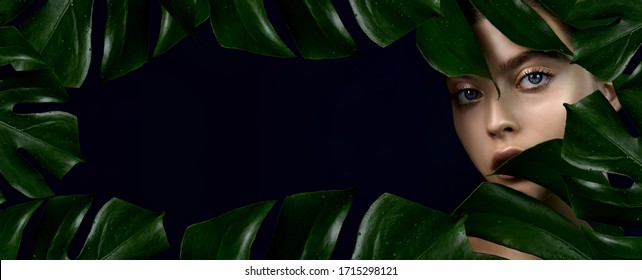 Young woman  with perfect skin arounded by tropical green leaves  frame on dark blue background with copyspace. Concept of natural organic cosmetics, SPA, wellness and skincare procedures.
