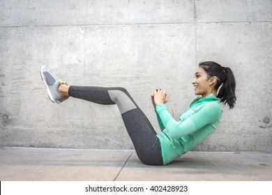 Young woman performing core crunch exercise - slight action blur in motion of activity = gritty urban outdoor location