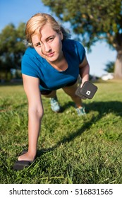 Young woman performing dumbbell row exercise lifting 12 pound weight in green grass outdoor park