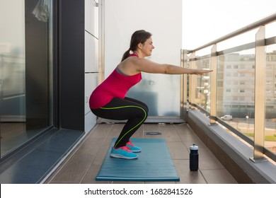 Young woman performing some workouts at his home terrace during coronavirus quarantine in Spain.