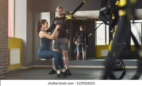 Young woman performing TRX training in gym with personal coach. Sporty girl doing stretching exercise with elastic rope, copy space