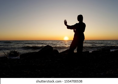 Young woman performing Wing Chun stance on the beach at sunset time. Concept of sports lifestyle.