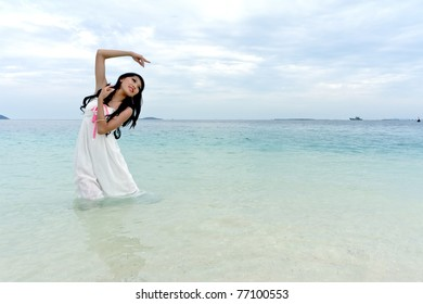 Young woman performs with raised hands on clear crystal beach of tropical island during holiday