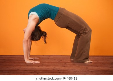 Young woman performs upward bow posture over orange background