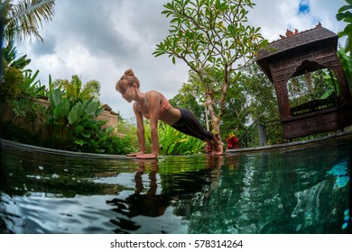 Young woman performs yoga exercises in the tropical garden by the pool