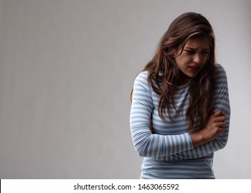 Young woman with a persecution complex reacting to rejection looking down with a troubled expression in a moody portrait over a grey studio background with copy space